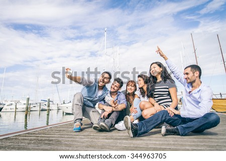 Best friends taking a self portrait - Group of young and happy people on vacation at harbor with sailing boats in the background - stock photo