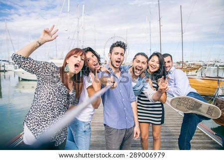 Best friends taking a self portrait with selfie stick - Group of young and happy people on vacation at harbor with sailing boats in the background - stock photo