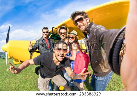 Best friends taking selfie at aeroclub with ultra light airplane - Happy friendship fun concept with young people and new technology trend - Sunny afternoon vivid color tones - Fisheye lens distortion - stock photo