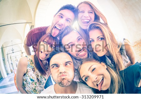 Best friends taking selfie outdoors with back lighting - Happy friendship concept with young people having fun together - Cold vintage filtered look with soft focus on faces due to sunshine halo flare - stock photo