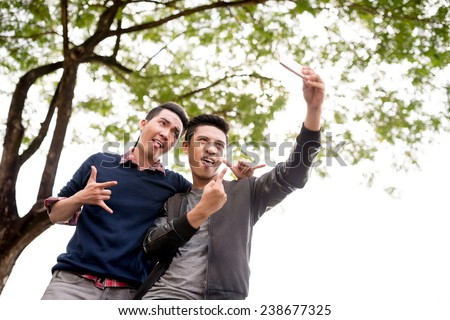 Best friends taking selfie with their tongues out - stock photo