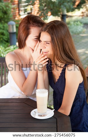 Best friends - teenage girls sitting at the cafe table, whispering and having fun.  - stock photo