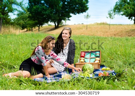 Best friends - two attractive young girls are having a picnic, dressed casual sitting on a blanket on the lawn in summer and chatting whilst eating fruits and sandwiches - stock photo