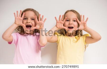 Best friends. Two cute little girls having a fun on grey background. - stock photo