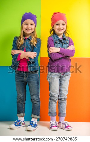 Best friends. Two cute little girls holding crossed hands on colorful background. - stock photo