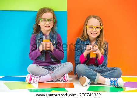 Best friends. Two cute little girls sitting on the floor and drinking juice on colorful background. - stock photo