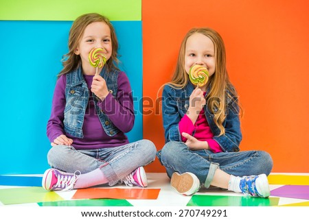 Best friends. Two cute little girls sitting on the floor and eating lollipop on colorful background. - stock photo