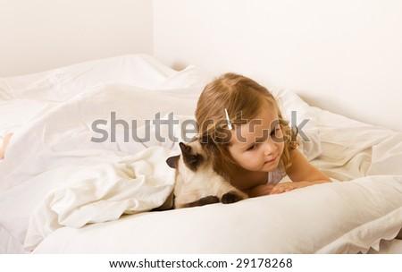 Best friends whispering - little girl with her kitten - stock photo
