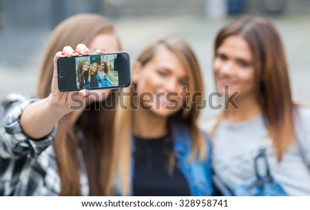 Best friends. Young friends girls are having fun together on the street and smile at each other. Funny and beautiful friends are doing selfie on cell phone - stock photo