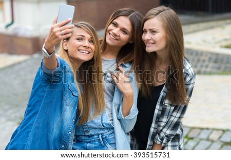 Best friends. Young friends girls are having fun together on the street and smile at each other. Beautiful girls friends are doing photo selfie on mobile cell phone - stock photo