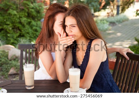 Best friends - young women sitting at the cafe table and whispering. - stock photo
