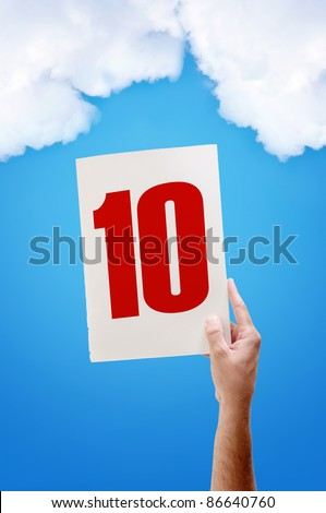 Best grade, excellent mark. White paper with number ten in male hand on blue sky background - stock photo