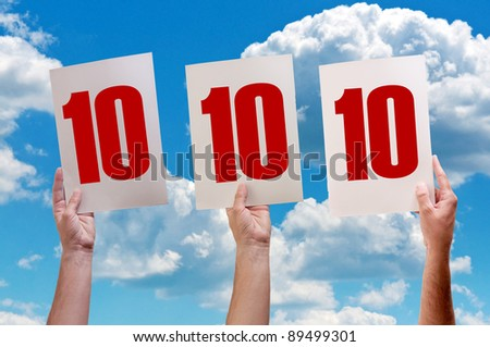 Best grades or best in class. Number ten on white paper held by three hands raised in air. - stock photo