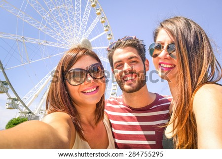 Best happy friends  with mobile taking selfie at ferris wheel - Three students at luna park - Concept of friendship and fun with new trend and technology - Young people enjoy with modern smartphone - stock photo