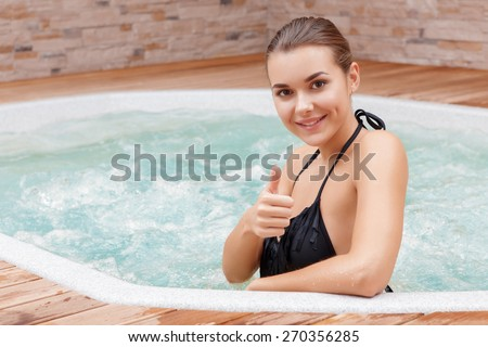 Best leisure. Young smiling woman showing her thumb up sitting in a jacuzzi in spa center - stock photo