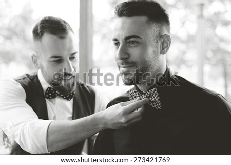Best man fixing groom's bow tie - stock photo