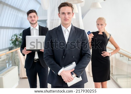Best Manager. Young man in formal wear holding a the tablet and smiling at the camera while his colleague talking on the background - stock photo