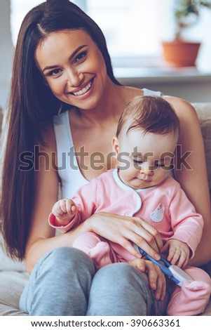 Best mom in the world. Beautiful young woman holding baby girl with toy on her knees and looking at camera with smile while sitting on the couch at home - stock photo