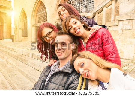 Best multiracial friends taking selfie outdoors in urban contest  - Happy friendship concept with young people having fun together - Soft focus on faces in the middle with sunshine halo flare  - stock photo
