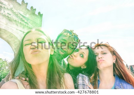 Best multiracial friends taking selfie outdoors with back lighting - Happy multirace friendship concept with young people having fun together - Cold vintage filtered look with  focus on left girl face - stock photo