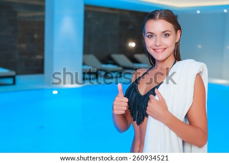 Best relaxation after the busy day. Closeup of gorgeous young woman in black bikini posing with towel on her shoulder and showing her thumb up while standing against spa swimming pool - stock photo