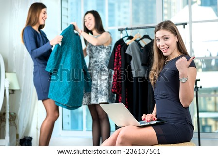 best sales. Smiling girl doing internet shopping in the laptop and showing thumbs up while her friend choose the dress on a hanger. Girls having fun together doing shopping - stock photo