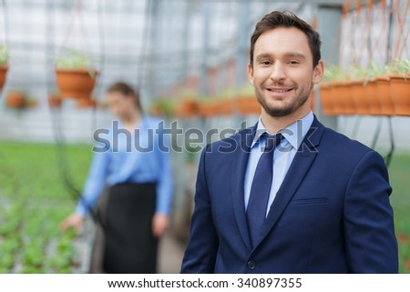 Best service for everyone. Positive smiling owner of greenhouse expressing gladness with his colleague standing in the background  - stock photo