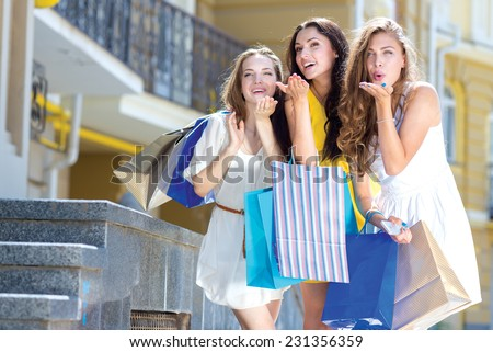 Best shopping wishes. Three young and pretty girls are standing with shopping bags. All are smiling and giving air kisses - stock photo