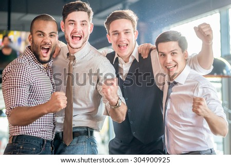 Best spending time in the bar. Four friends standing arm in arm at the bar and look at the TV and shout loudly and laughing. Friends having fun together - stock photo