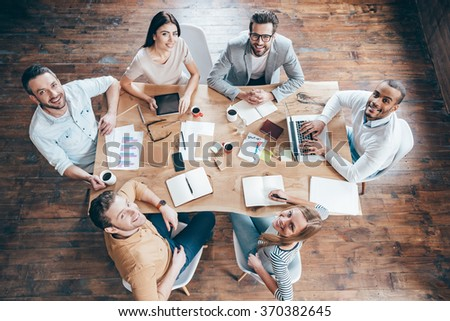 Best team ever! Top view of group of six people looking at camera with smile while sitting at the office table - stock photo