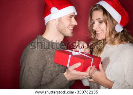 Best time of the year. Studio portrait of a young loving Christmas couple opening a present together laughing happily against red background - stock photo