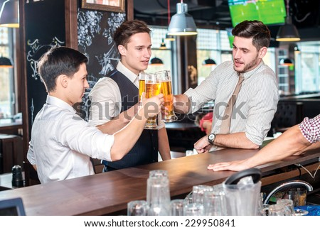 Best to spend the evening with friends. Three cheerful friends met at the bar and clink glasses of beer while the bartender is standing on the bar. Friends having fun together - stock photo