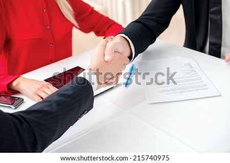 Best Trade. Three successful and confident businessman shaking hands. Businesspeople in formal dress sitting in an office at a desk close-up view of hands - stock photo