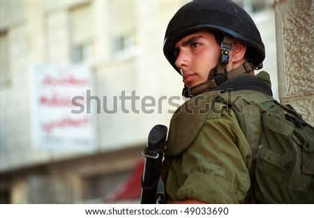 BETHLEHEM, PALESTINIAN AREAS - MAY 28: A soldier of the Israeli Defense Forces patrols the West Bank town of Bethlehem during a curfew imposed on its Palestinian residents May 28, 2002 in Bethlehem. - stock photo