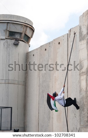 BETHLEHEM, PALESTINIAN TERRITORIES - MARCH 30: A Palestinian scales the Israeli separation wall during clashes at the Bethlehem checkpoint during Land Day protests on March 30, 2012. - stock photo