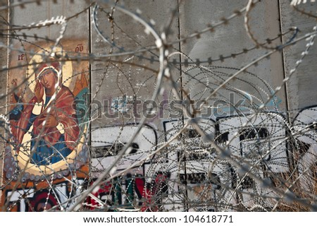 BETHLEHEM, PALESTINIAN TERRITORIES - MARCH 10: An icon of St. Mary is painted on the Israeli separation wall in the West Bank town of Bethlehem, March 10, 2012. - stock photo