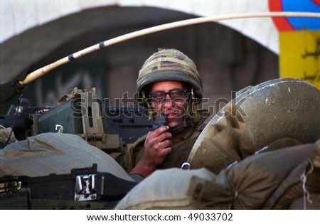 BETHLEHEM, PALESTINIAN TERRITORIES - MAY 28: An Israeli soldier patrols the West Bank town of Bethlehem in a tank during a curfew imposed on its Palestinian residents May 28, 2002 in Bethlehem. - stock photo
