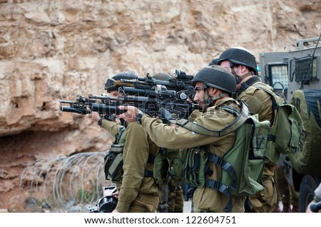 BETHLEHEM, PALESTINIAN TERRITORY - NOVEMBER 14: Israeli soldiers aim  rifles equipped with grenade launchers for firing tear gas during a demonstration near Bethlehem, West Bank, November 14, 2012. - stock photo
