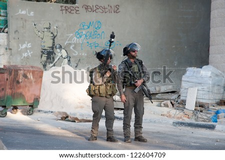 BETHLEHEM, PALESTINIAN TERRITORY - NOVEMBER 20: Israeli soldiers occupy Bethlehem, West Bank, streets near a mural by the artist Banksy during protests against Israeli attacks on Gaza, Nov. 20, 2012. - stock photo