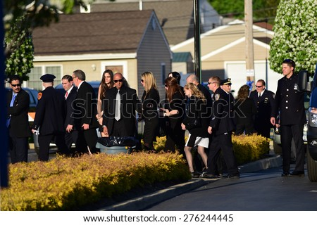 BETHPAGE, LONG ISLAND - MAY 7 2015: a formal viewing for slain NYPD officer Brian Moore, attended by thousands of police officers from North America. Family of Brian Moore escorted into funeral home - stock photo