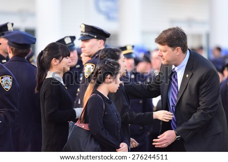 BETHPAGE, LONG ISLAND - MAY 7 2015: a formal viewing for slain NYPD officer Brian Moore, attended by thousands of police officers from North America. Pei Xia Chen, widow of Wenjian Liu, is embraced - stock photo