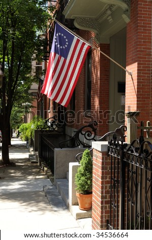 Betsy Ross flag waving on the street of Charlestown, in Boston, Massachusetts. It was designed during the American Revolution and features 13 stars to represent the original colonies. - stock photo