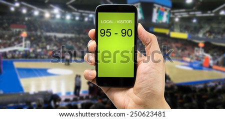 betting man through his smart phone in a basketball arena - stock photo