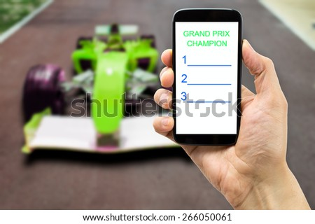 betting man through his smart phone in a car circuit - stock photo