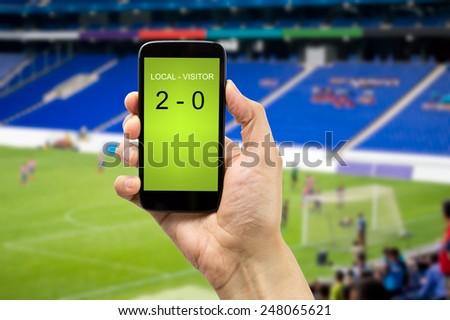betting man through his smart phone in a stadium - stock photo
