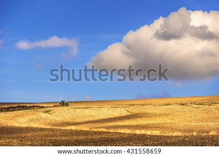 Between Apulia and Basilicata: rural hilly landscape. ITALY.Tractor dominated by a cloud. - stock photo