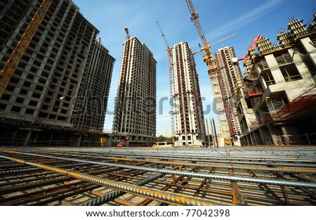 Between tall buildings under construction and cranes under a blue sky - stock photo