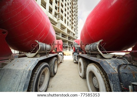 Between two concrete mixer standing near unfinished tall high-rise buildings - stock photo