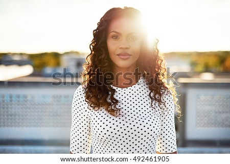 Beuatiful woman standing tall with sun behind shining brightly behind her outdoors