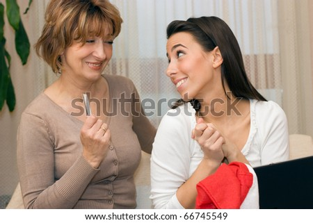 Beutiful young daughter and  her mother sitting on the sofa and shopping on-line . - stock photo